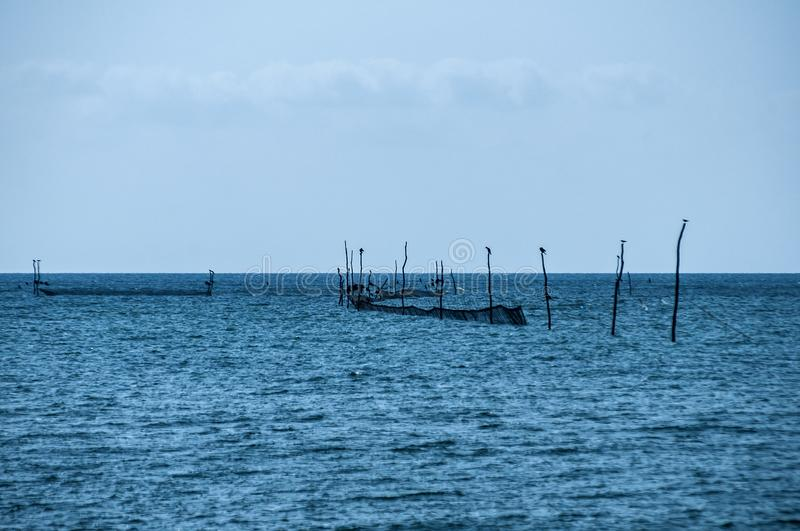Fishing sea trap equipment. Fishing trap equipment with fishing networks in blue sea waters on blue sky background stock image