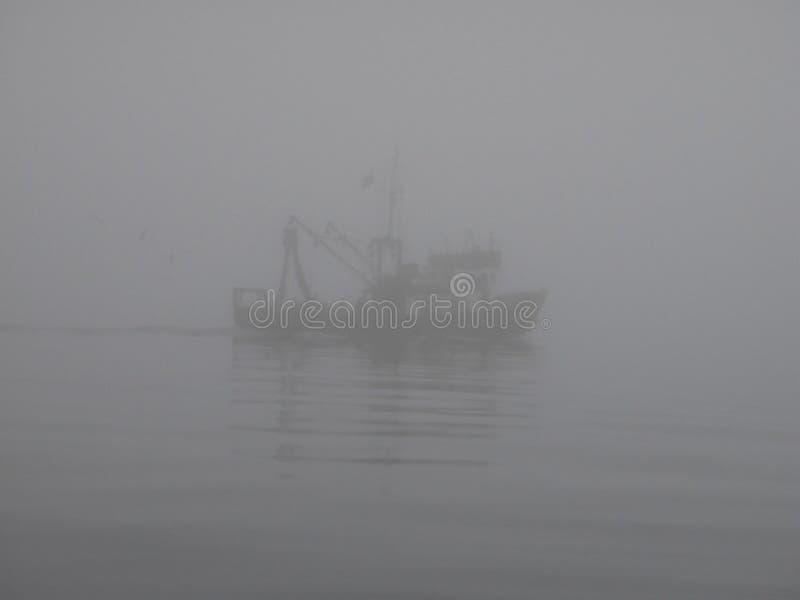 Fishing ship in fog stock photo