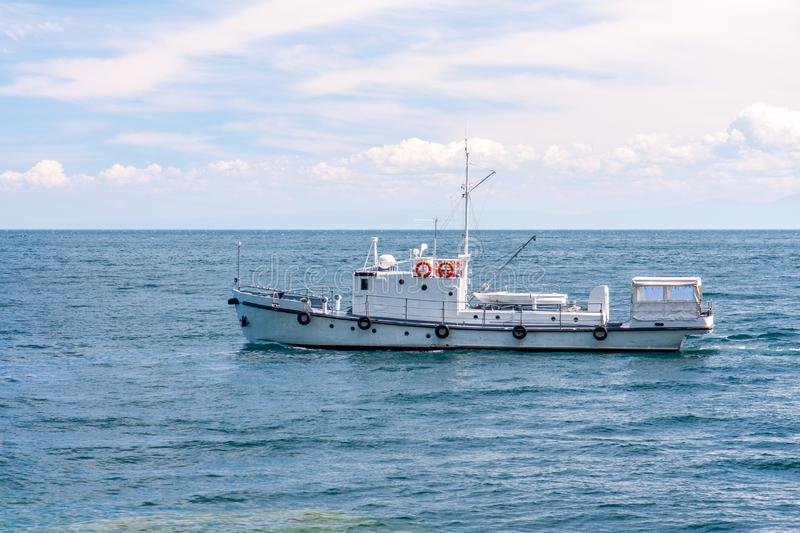 Fishing ship on the water surface in clear weather royalty free stock image