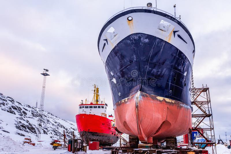 Fishing ships hulls in dockyard on maintenance during the winter time, port of Nuuk, Greenland royalty free stock image