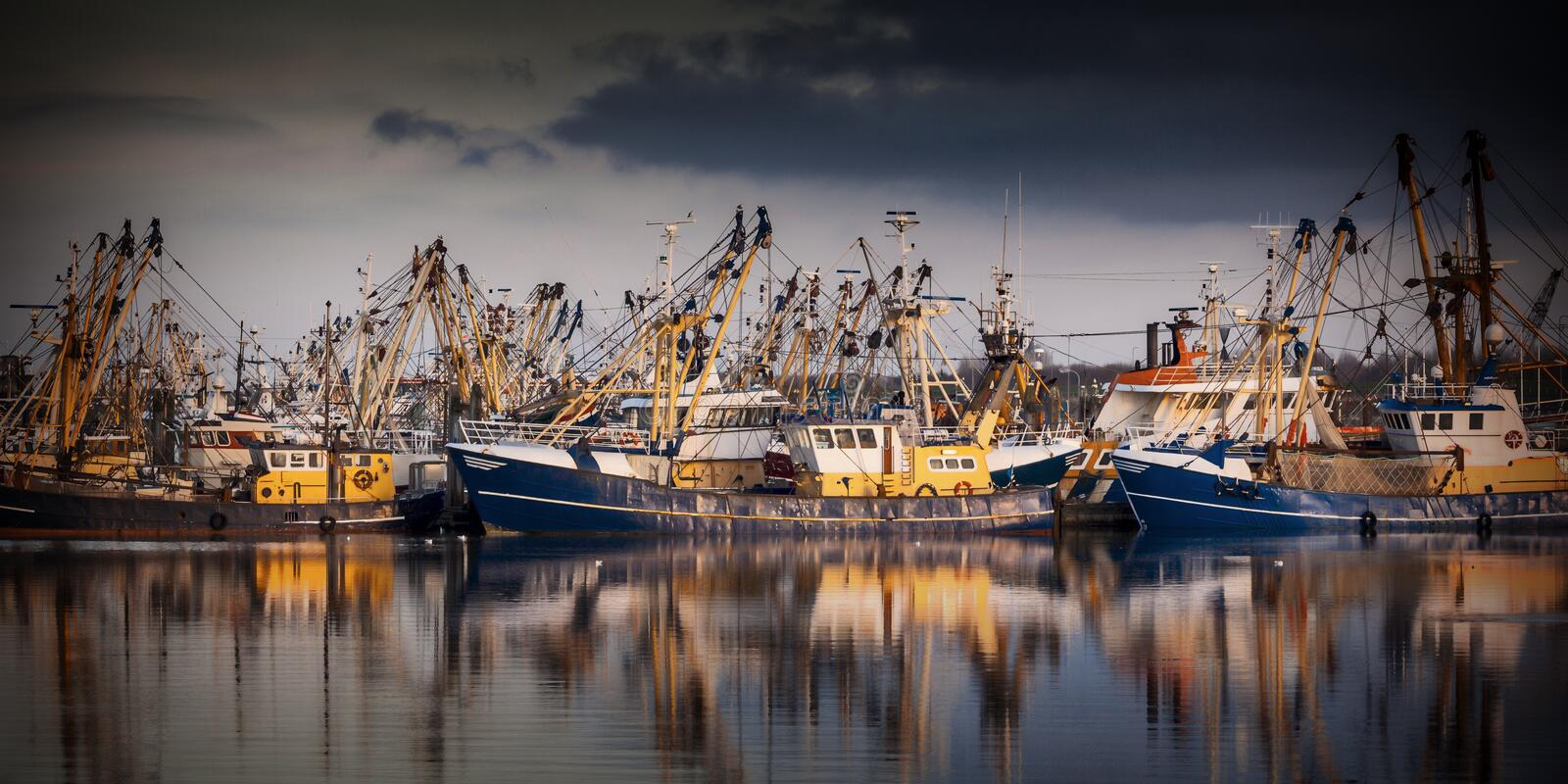 Fishing ships during majestic sunset. Fishing ships in Lauwersoog. Which harbours one of the biggest fishing fleets of the Netherlands. The fishery concentrates stock image