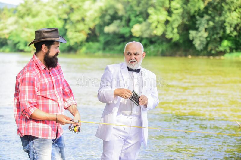 Fishing skills. Fish with companion who help in emergency. Men friends relaxing river background. Personal instructor. Expert fisherman. Bearded men elegant royalty free stock image
