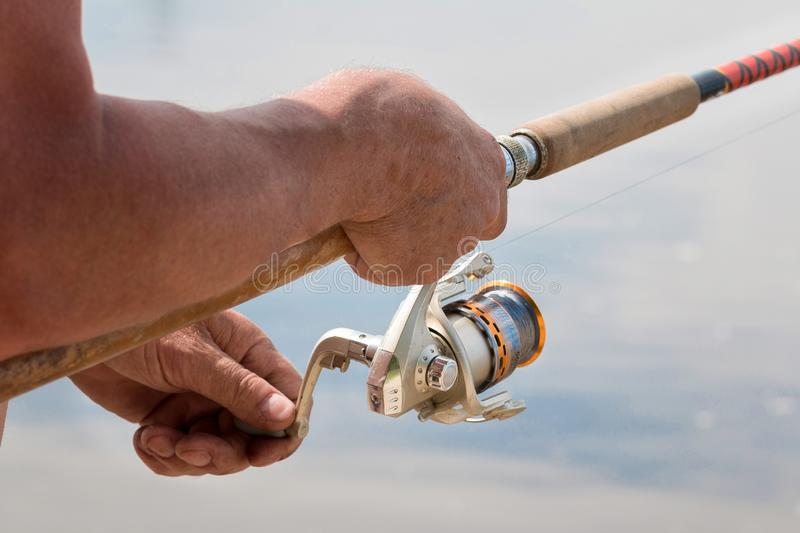 Fishing with a spinning on the river. Man catches fish, a close up of a hand and the spinning reel. In sammer day. Hobby, vacation, pastime stock images