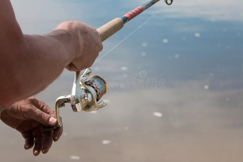 Fishing with a spinning on the river. Man catches fish, a close up of a hand and the spinning reel. In sammer day. Hobby, vacation, pastime royalty free stock images