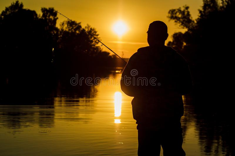 Fishing. spinning at sunset. Silhouette of a fisherman. royalty free stock images
