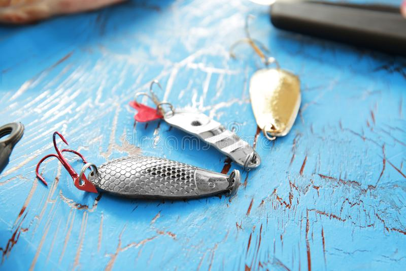 Fishing spoon baits on wooden table, royalty free stock image