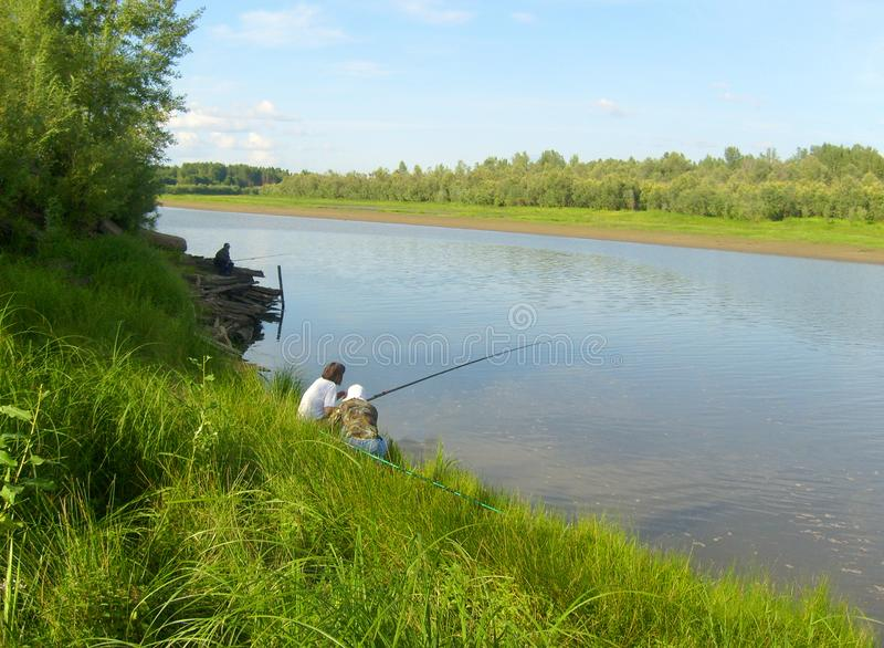 Fishing summer fine afternoon. Landscape with river, green grass, clear sky. Siberian river stock photos