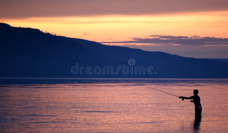 Fishing at sunset royalty free stock photography