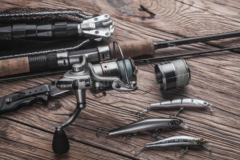 Fishing tackle for catching predatory fish. Wobblers, spinning, reel, fishing line. On the wooden background royalty free stock image