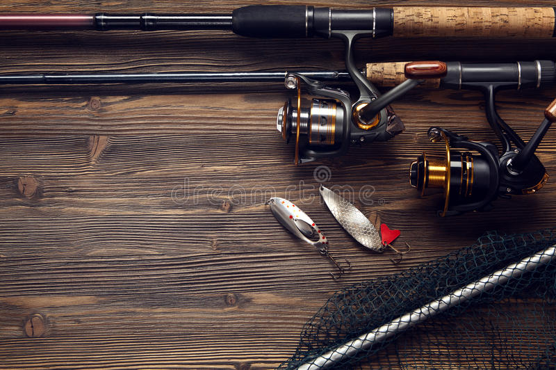 Fishing tackle - fishing spinning, hooks and lures on wooden background. stock photography