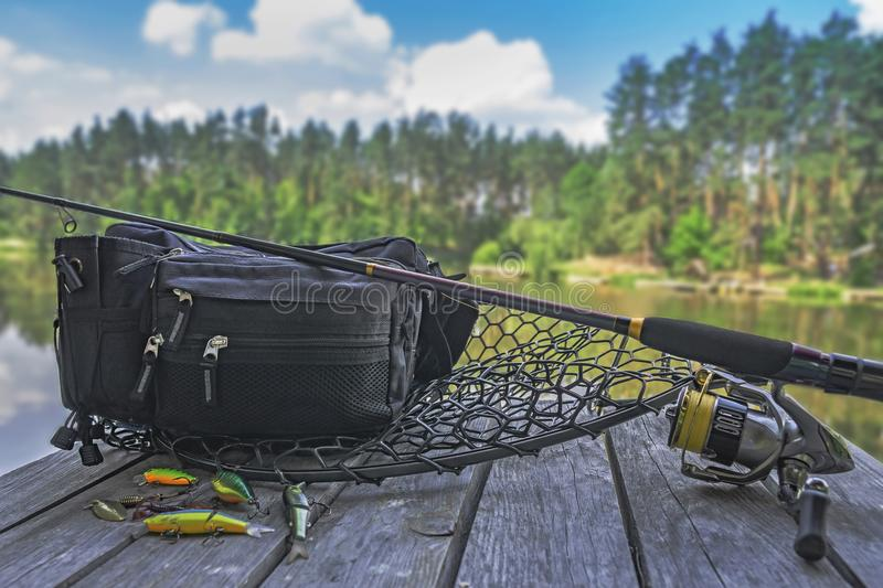 Fishing tackle set. Spinning rod with reel and lures on wooden platform on forest lake stock images