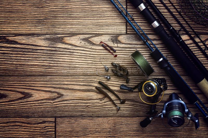 Fishing tackle - fishing spinning, hooks and lures on darken wooden background. Top view. Copy-space. Fishing tackle - fishing spinning, hooks and lures on royalty free stock images