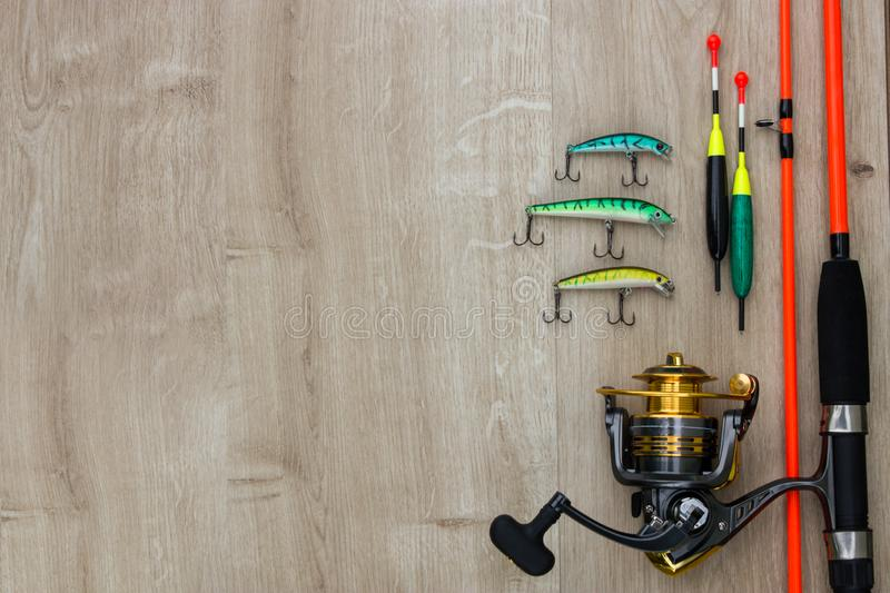 Fishing tackle - fishing spinning, hooks and lures on white wooden background.Top view. Color spinner lures, fishing bytes, floats, spinning reel and orange rod stock photo