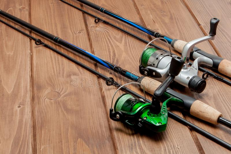 Fishing tackle - fishing spinning, hooks and lures on wooden background with copy space.  stock image