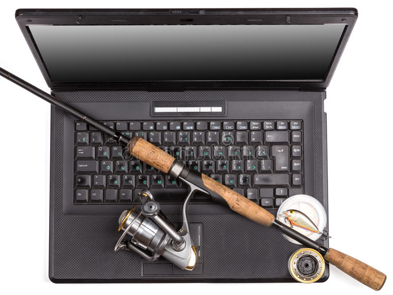 Fishing tackles on keyboard a black notebook. Different fishing tackles on dark keyboard a black notebook. Concept design for freshwater outdoor active business royalty free stock image