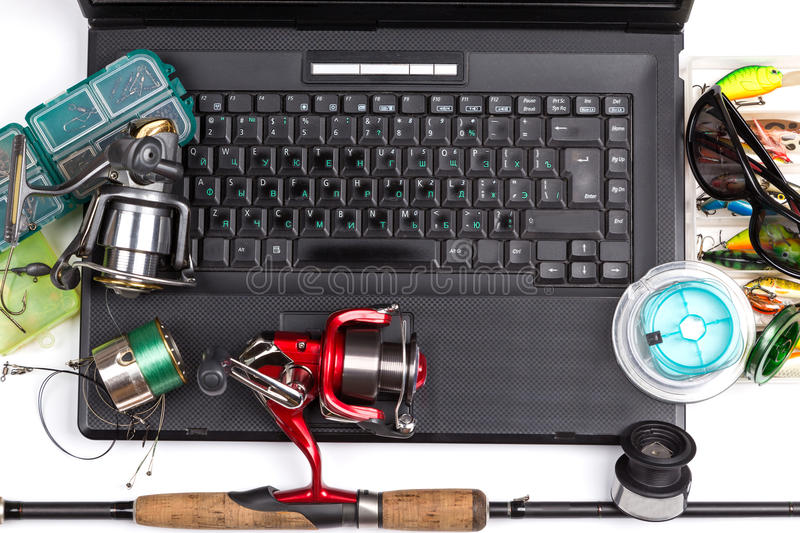 Fishing tackles on keyboard a black notebook. Different fishing tackles on dark keyboard a black notebook. Concept design for freshwater outdoor active business royalty free stock photography