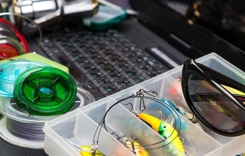 Fishing tackles on keyboard a black notebook. Different fishing tackles on dark keyboard a black notebook. Concept design for freshwater outdoor active business stock photography