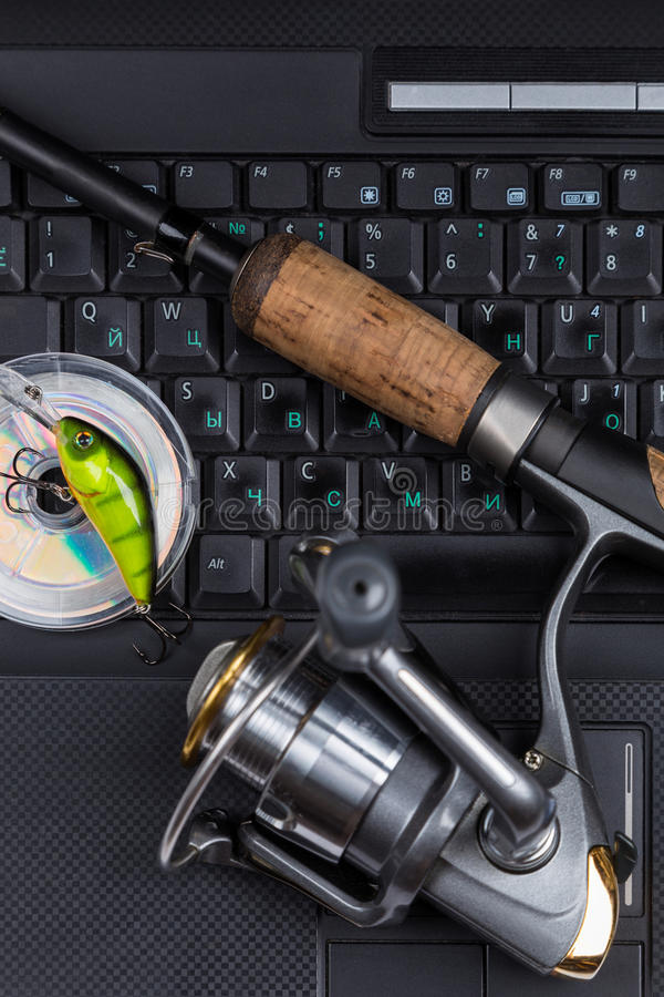 Fishing tackles on keyboard a black notebook. Different fishing tackles on dark keyboard a black notebook. Concept design for freshwater outdoor active business stock photos