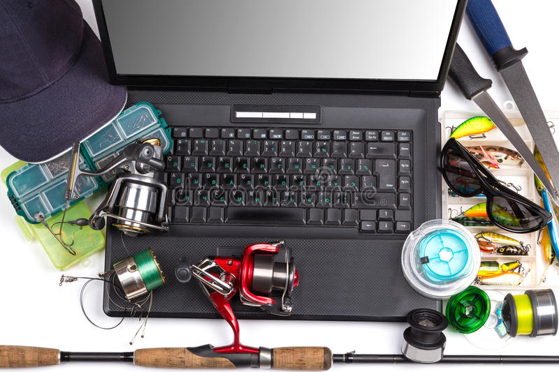 Fishing tackles on keyboard a black notebook. Different fishing tackles on dark keyboard a black notebook. Concept design for freshwater outdoor active business royalty free stock images