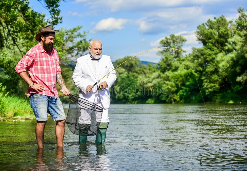 Fishing team. Active day. Family day. Hobby and recreation. Peace of mind and tranquility. Freshwater fish. Bearded man stock photography