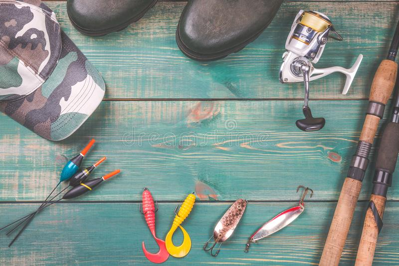 Fishing theme. background from fishing rods with fishing tackles, rubber boots, camouflage cap and fishing buoy on green wooden ba. Ckground with copy space stock photography