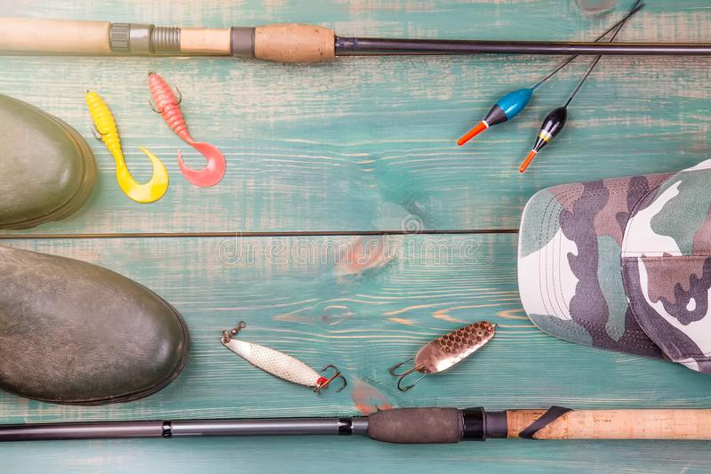 Fishing theme. Frame from fishing rods with fishing tackles, rubber boots, camouflage cap and fishing buoy on green wooden backgro. Und stock photography