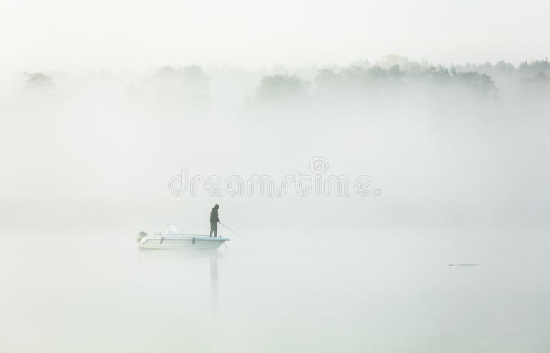 Fishing in a thick morning fog royalty free stock photo