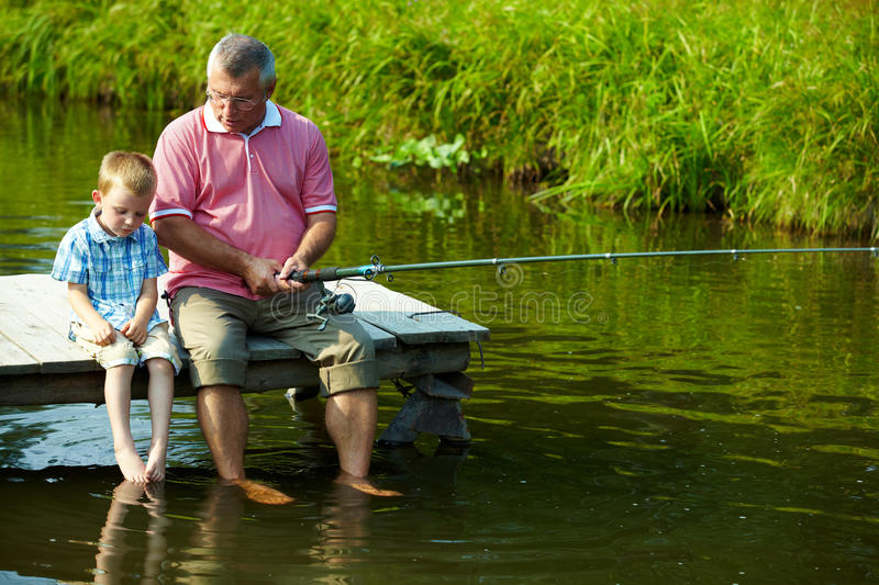 Fishing time. Photo of grandfather and grandson sitting on pontoon with their feet in water and fishing on weekend