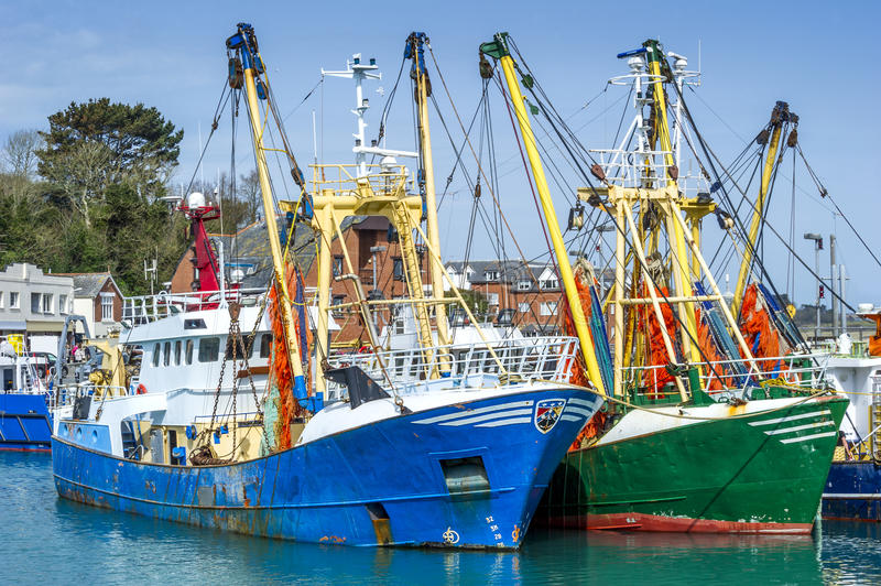 Fishing Trawlers in Port. Rusty fishing trawlers moored in the port of a small fishing village stock photography