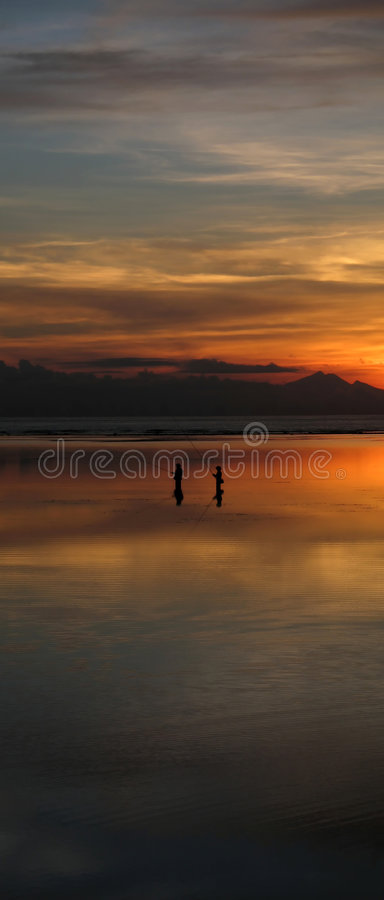 Fishing Under a warm Sunrise. On Sanur Beach, Bali, Indonesia royalty free stock image