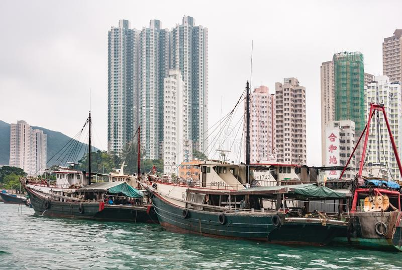 Fishing vessels docked in front of tall buildings in harbor of Hong Kong, China. Hong Kong, China - May 12, 2010: Black and red fishing vessels docked in harbor stock photography