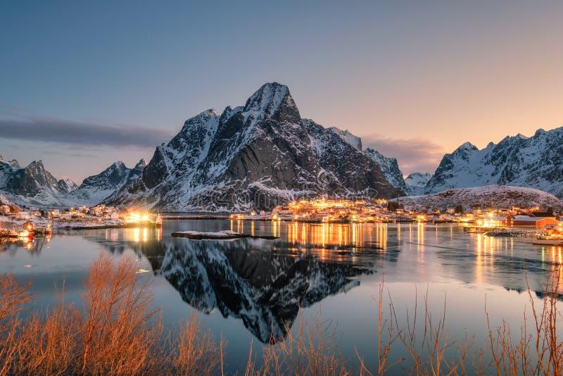 Fishing village illumination with mountain range reflection on coastline at dawn royalty free stock photography
