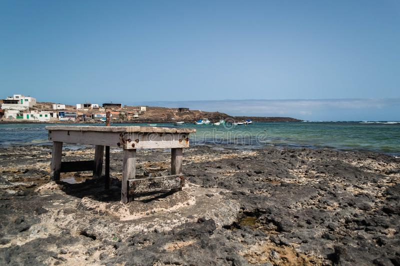 Fishing village, table on the shore of the beach with rocks. Fuerteventura, Canary Islands. royalty free stock images