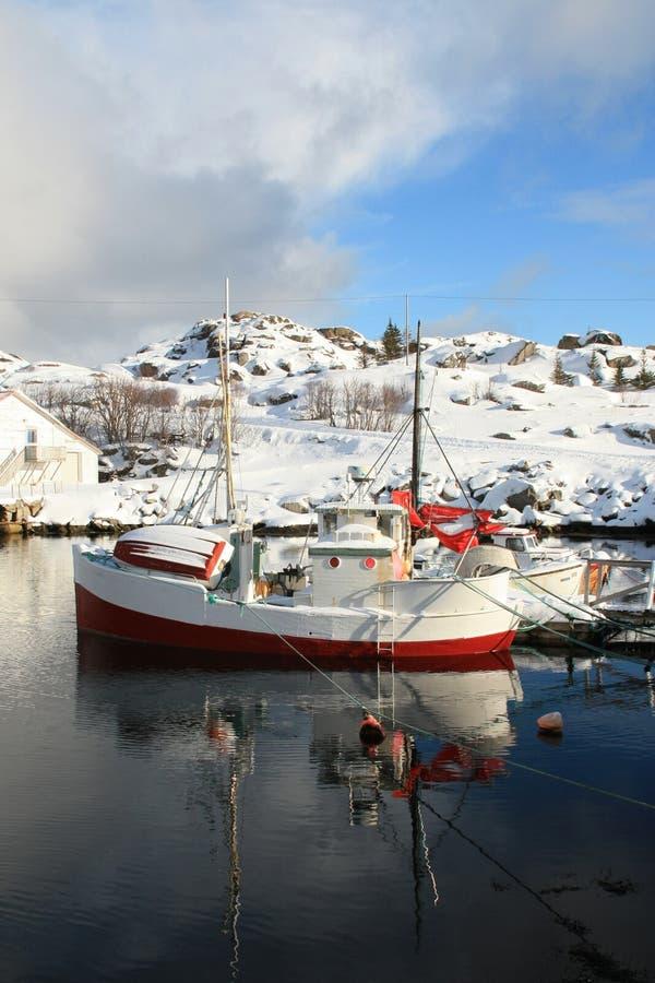 Fishingboat mirroring in Kraemmervika. An old traditional boat in the innerst part harbour of Kraemmervika in Lofoten islands stock image