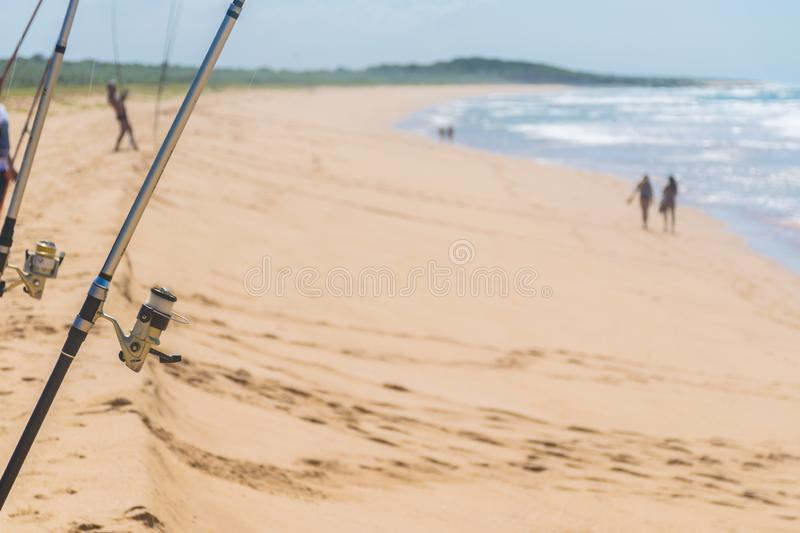 Fishingrods are stuck in the sand, footprints in several directions, a man is pulling his fishing rod, to couples walk royalty free stock image
