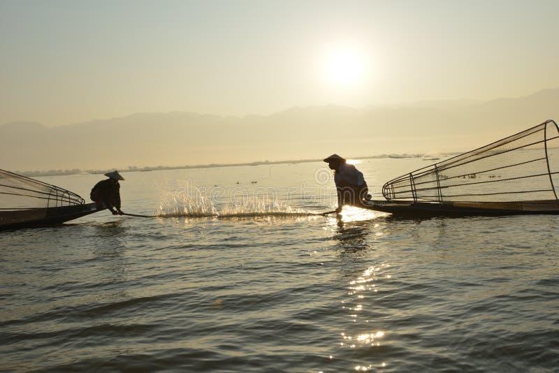 Fishman e rete nell'alba della canoa fotografia stock libera da diritti