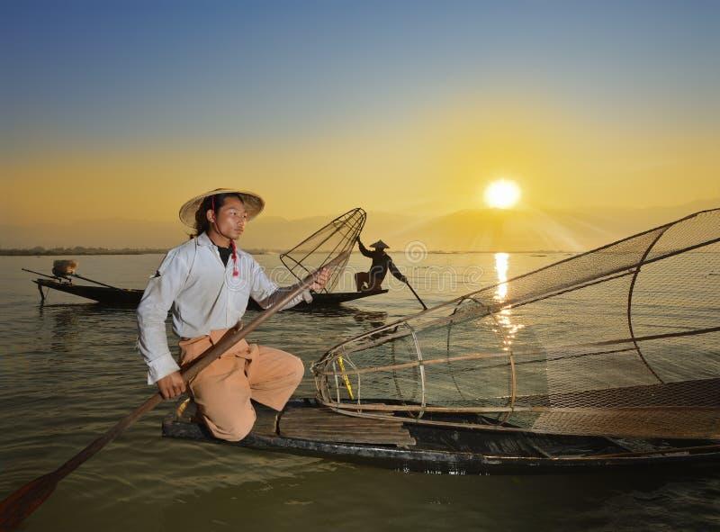 Fishman e rete nell'alba della canoa fotografie stock libere da diritti