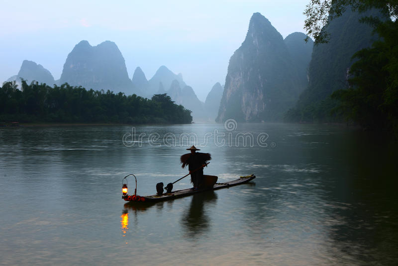Fishman en el amanecer del río Lijiang foto de archivo