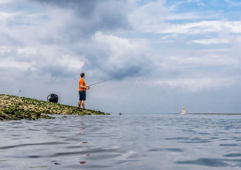 Fishman fishing by lakeside, kings park long island ny. Fish man fishing by lakeside with a dramatic stormy sky long island kings park NY 11754 royalty free stock images