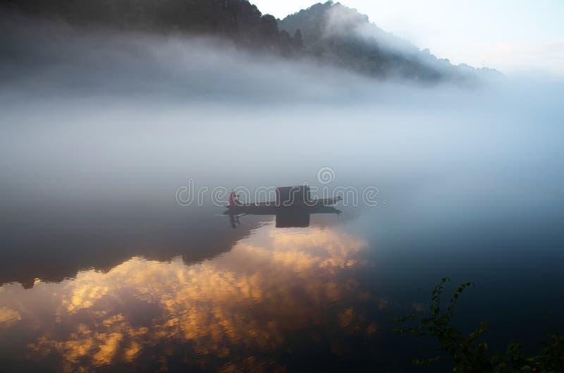 Fishman op de boot in de mist op de rivier, de gouden wolkenbezinning op de oppervlakte van water, bij dageraad stock afbeeldingen