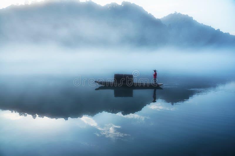 Fishman op de boot in de mist op de rivier, de gouden wolkenbezinning op de oppervlakte van water, koude toon stock afbeelding