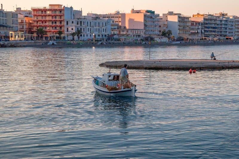 Fishman sur le bateau au lever de soleil tôt dans Loutraki photos libres de droits