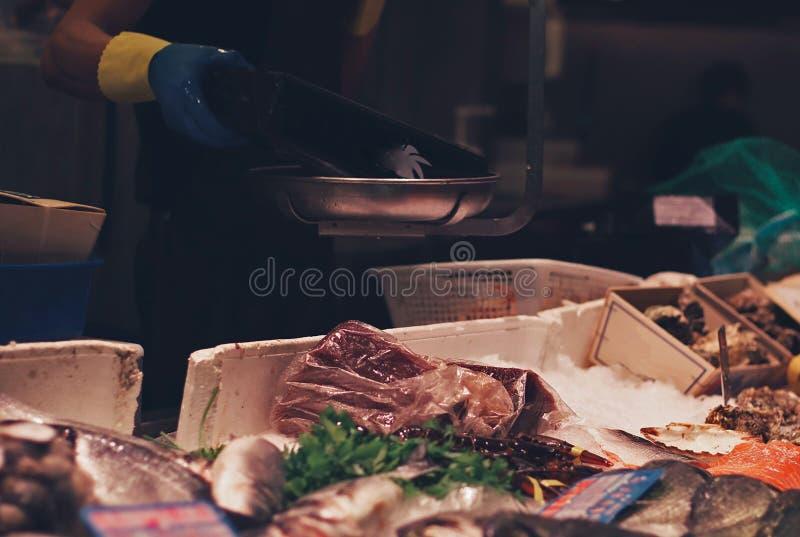 Fishmonger ψάρια ζυγίσματος στην αγορά στοκ φωτογραφίες με δικαίωμα ελεύθερης χρήσης