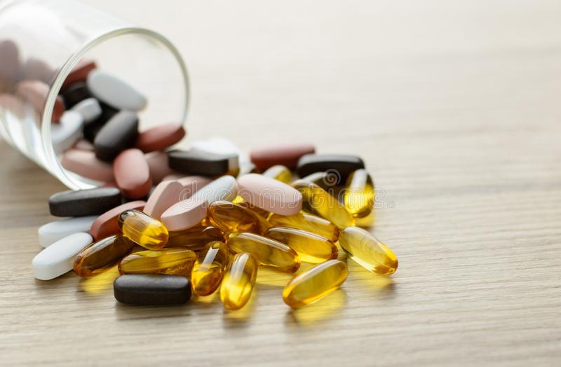 Fishoil capsules and Multivitamin supplements out of the small glass on the wooden table. With copy space stock photo