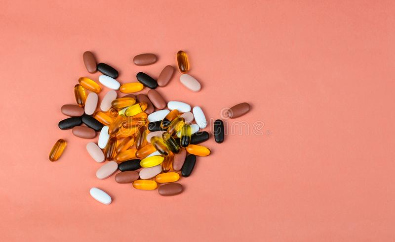 Fishoil capsules and Multivitamin supplements. On the pink background with copy space stock images
