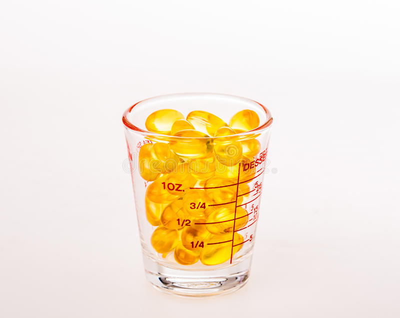 Fishoil in measuring cup. Isolated fishoil in measuring cup royalty free stock photo
