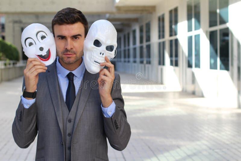 Fishy businessman holding scary masks isolated royalty free stock photo