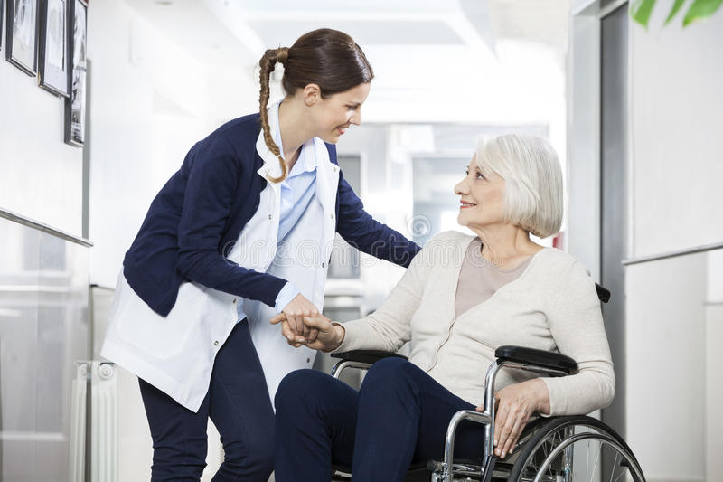 Fisioterapeuta Consoling Senior Woman que senta-se na cadeira de rodas imagens de stock royalty free