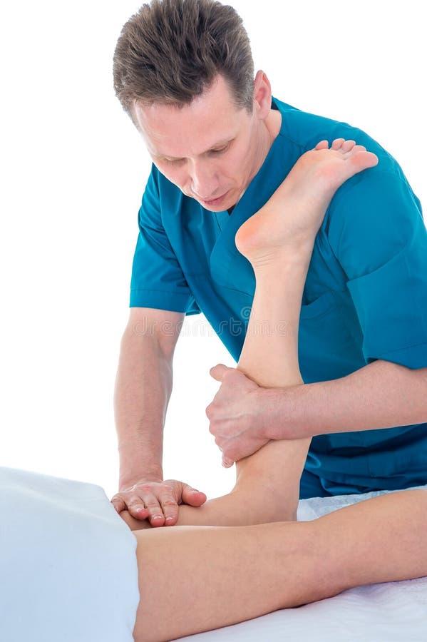 Fisioterapeuta, dando masajes a la pierna del paciente en el cuarto de la fisioterapia, concepto de rehabilitación de la fisioter imagenes de archivo