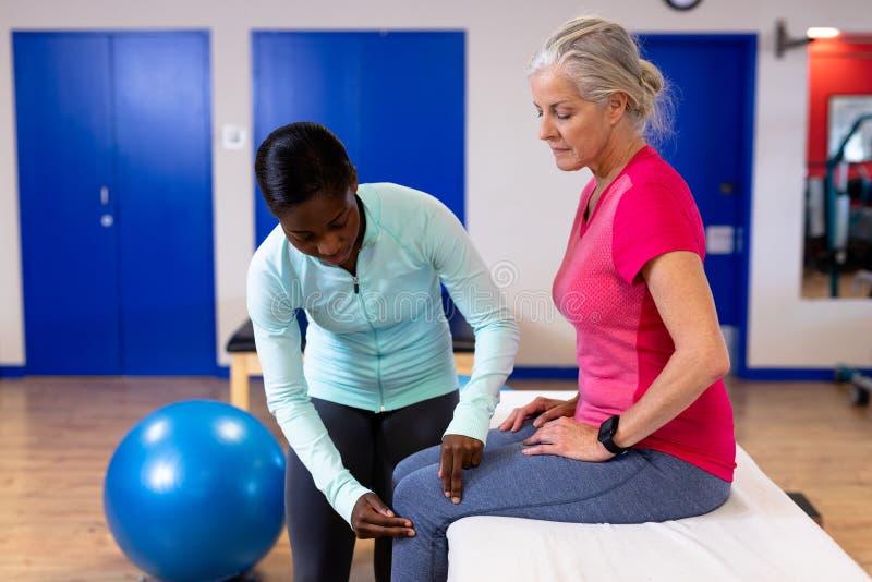 Fisioterapeuta de sexo femenino que examina la pierna mayor activa de la mujer en centro de deportes imagen de archivo libre de regalías
